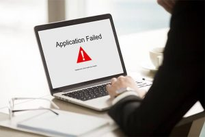 An image featuring a person using their laptop that says application failed on it