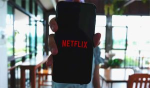 An image featuring Netflix concept with a person holding their phone that has Netflix opened