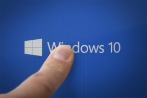 An image featuring a person pointing his index finger on the Windows 10 logo and text